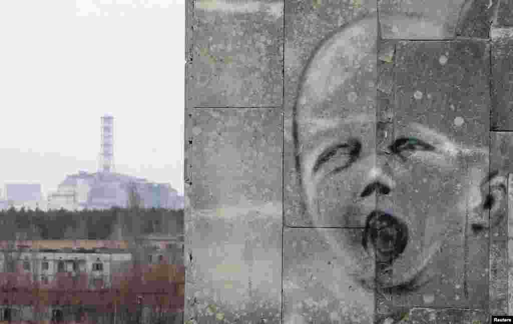 Иен қалған Припять қалашығындағы үйдің қабырғасына салынған жылап тұрған жас баланы бейнелейтін граффити. Сырт жағында апат болған Чернобыль АЭС-нің №4 блогы көрініп тұр. 4 сәуір 2011 жыл. 4 сәуір 2011 жыл.