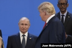 U.S. President Donald Trump (right) looks at President Vladimir Putin as they line up for a photo at the G20 summit in Buenos Aires.