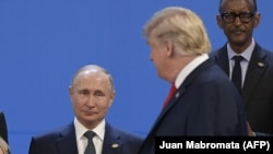 US President Donald Trump (R), looks at Russia's President Vladimir Putin as they take place for a family photo, during the G20 Leaders' Summit in Buenos Aires, on November 30, 2018