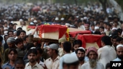 Relatives and residents carry the coffins of bomb victims during a funeral procession of victims of a Peshawar bombing in late September.