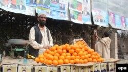 Продавец фруктов на фоне агитационных плакатов кандидатов в президенты Афганистана. Джелалабад, 3 февраля 2014 года.