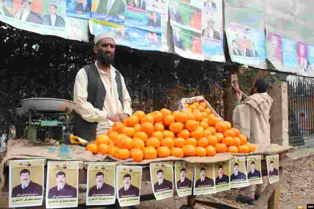 A fruit vendor's stall in the eastern city of Jalalabad is decorated with campaign posters belonging to presidential candidate Gul Agha Sherzai.