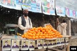 Продавец фруктов на фоне предвыборных плакатов. Джалалабад, 3 февраля 2014 года.