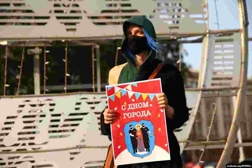 Женщина держит в руках плакат«С Дном города»