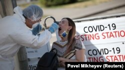 A Kazakh health worker takes a swab from a woman at a mobile testing station for COVID-19 in Almaty earlier this week.