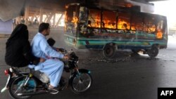 A Pakistani family rides past a burning bus during a week of violence in the restive city of Karachi.