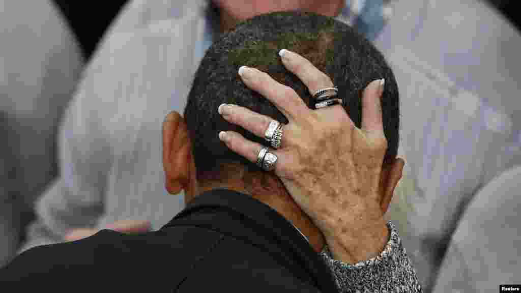 A woman grasps the head of U.S. President Barack Obama as he greets supporters at a campaign event at Springfield High School in Ohio. (Reuters/Larry Downing)