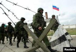 Военные, предположительно российские, маршируют близ украинской воинской части в селе Перевальное близ Симферополя. 4 марта 2014 года.