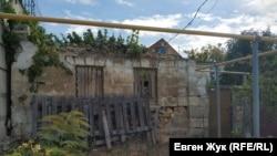 К «банковскому» забору примыкает старый полуразрушенный дом