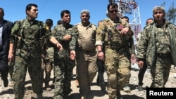 A U.S. military commander (2nd right) walks with Kurdish fighters from the People's Protection Units (YPG) at the YPG headquarters that was hit by Turkish air strikes in Mount Karachok near Malikiya, Syria, on April 25.