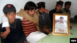 Mujtaba Hasan (second from left) with a picture of his brother of Atizaz, who reportedly sacrificed his life to stop a suicide bomber outside his school.