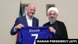 A handout picture released by the office of Iranian President Hassan Rouhani shows him (R) and FIFA President Gianni Infantino holding a football shirt with Rouhani's name during Infantino's visit to the capital Tehran on March 1, 2018.