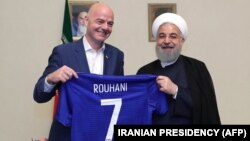Iranian President Hassan Rohani (right) and FIFA President Gianni Infantino hold up a soccer shirt with Rohani's name during Infantino's visit to Tehran in March 2018.