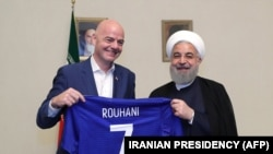 A handout picture released by the office of Iranian President Hassan Rouhani shows him (R) and FIFA President Gianni Infantino holding a jersey with Rouhani's name during Infantino's visit to the capital Tehran on March 1, 2018.