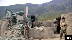 FILE: Afghan soldiers inspect their checkpost damaged in a militant attack in Kunar.