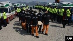 Участники поисковой операции несут тело одной из жертв трагедии