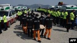 Құтқарушылар суға батқан кеменің орнынан табылған мәйітті әкетіп барады. Оңтүстік Корея, 20 сәуір 2014 жыл.