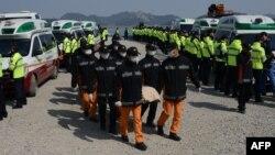 Рятувальники несуть тіло загиблого внаслідок аварії на поромі у Південній Кореї