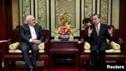 Iranian Foreign Minister Mohammad Javad Zarif (L) and his Chinese counterpart Wang Yi iduring their meeting at the Diaoyutai State Guesthouse in Beijing, China February 19, 2019. How Hwee Young/Pool via REUTERS