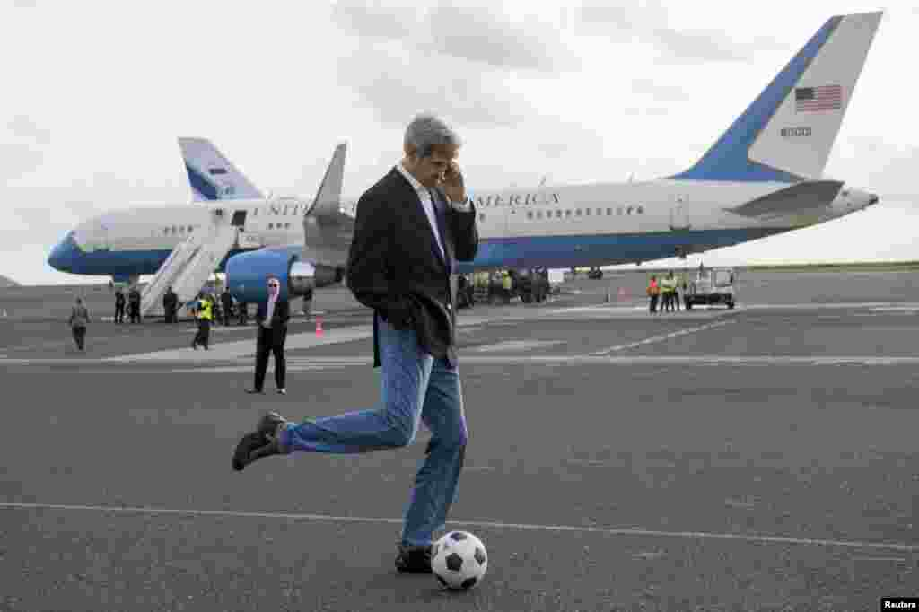 U.S. Secretary of State John Kerry kicks a soccer ball while talking on his cellphone during an airplane refuelling stop en route to Washington on May 5. (Reuters/Saul Loeb)