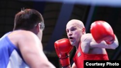 Казахстанский боксер Василий Левит (в красном) на ринге против соперника из Узбекистана Санжара Турсунова. Ташкент, 3 мая 2017 года.
