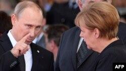 Президент России Владимир Путин беседует с канцлером Германии Ангелой Меркель вскоре после аннексии Крыма. Нормандия, 6 июня 2014 года.