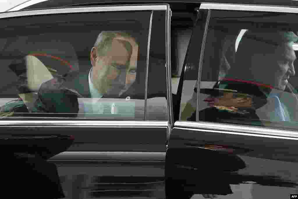 The honor guards are reflected in the limousine carrying Russian President Vladimir Putin as he arrives at the opening day of the World Climate Change Conference 2015 (COP21), at Le Bourget, on the outskirts of Paris, on November 30. (AFP/Christophe Ena)