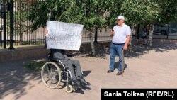36-летний житель столицы Ермек Бекишев, у которого установлена первая группа инвалидности, проводит одиночный пикет у здания МВД с требованием отставки министра внутренних дел Ерлана Тургумбаева. Нур-Султан, 9 августа 2019 года.