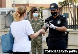 A police officer inspects a woman's documents under the gaze of an Azerbaijani soldier in Baku in July during the coronavirus pandemic. Azerbaijan deployed troops to help police ensure a tight coronavirus lockdown in the capital and several major cities.