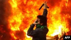 An opposition supporter gestures next to a burning police motorcycle set on fire during clashes with security forces in Tehran on December 27.