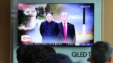 People watch a TV screen showing file footage of U.S. President Donald Trump, right, and North Korean leader Kim Jong Un during a news program at Seoul Railway Station in Seoul, South Korea, Monday, June 11, 2018.