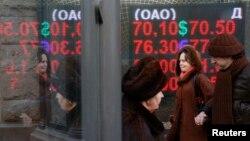 Прохожие в Москве рядом с электронным табло с курсами покупки и продажи валют. 16 декабря 2015 года.