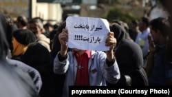 "People gathered in front of the governorate of Fars, on January 09, 2017, in protest against satellite jamming emissions in Shiraz. One of the protesters holds a sign that reads ""Shiraz, the capital of parasite""."