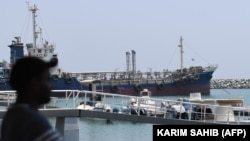 UAE -- A man watches on July 2, 2019 the ships movement in the port of Fujairah in the east of the United Arab Emirates (UAE), where recent tensions spiraling between Iran and the United States have affected movement in the Gulf of Oman, near the strategi