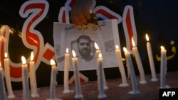 Свечи на фоне погибшего при взрыве в Пакистане оператора новостной службы.