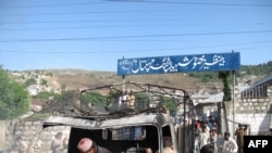Pakistani gather around the wreckage of a police truck torched by demonstrators in Abbottabad on April 12.