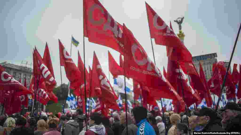 Колона із декількох сотень людей із червоними прапорами проходить повз майдан Незалежності