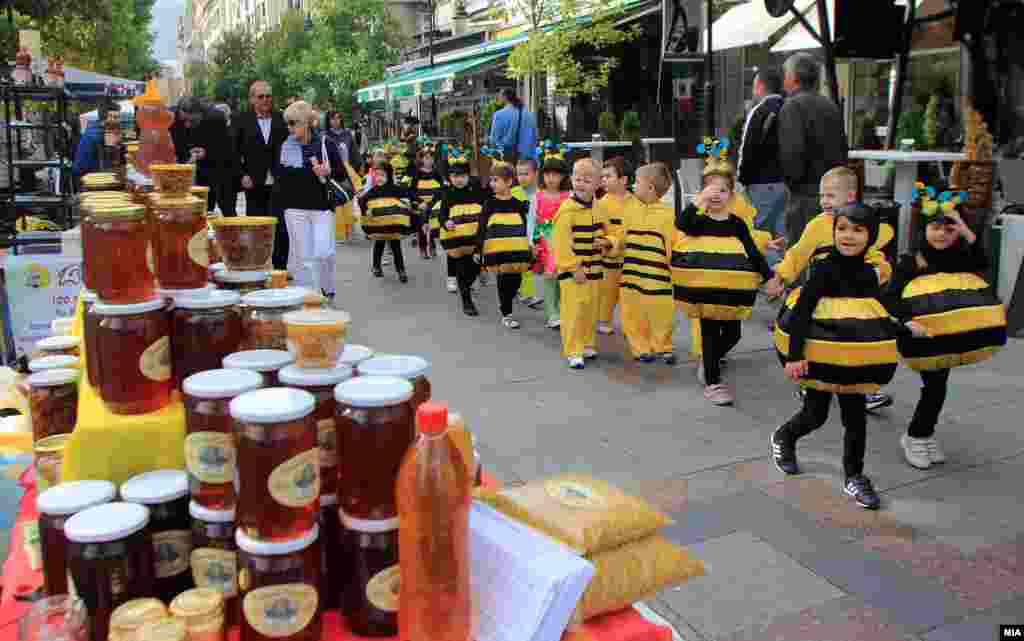 Children in costume march past stands as part of Macedonian Honey Days.