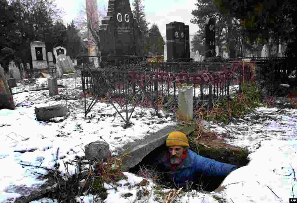 A homeless man, Bratislav Jovanovic, 43, enters a grave that he uses as a shelter during winter at a cemetery in Nis, 200 kilometers south of Belgrade. Jovanovic has been homeless for nearly 20 years, since his house burned down. For the last 15 years he has lived in a tomb beside the caskets of his descendants. (AFP/Sasa Djordjevic)