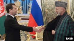 Russian President Dmitry Medvedev (left) greets Afghan President Hamid Karzai in Moscow.