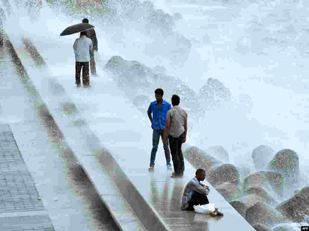 Indian pedestrians walk along the coast in Mumbai during the height of the monsoon. Photo by Punit Paranjpe for AFP