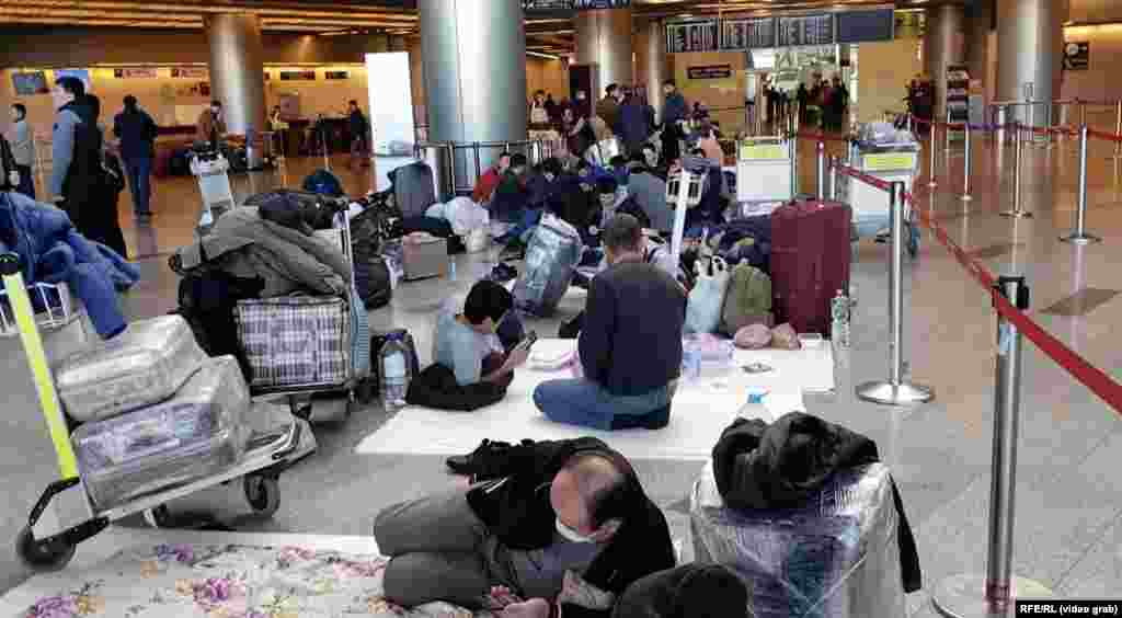 Uzbek migrant workers sprawl out on the floor at Vnukovo International Airport outside Moscow.