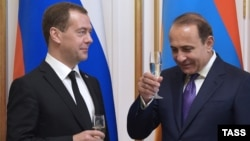 Russia - Russia's Prime Minister Dmitry Medvedev (L) and Armenia's Prime Minister Hovik Abrahamyan hold glasses of champagne during a ceremony of signing joint documents following Russian-Armenian talks, Yerevan, April 07, 2016
