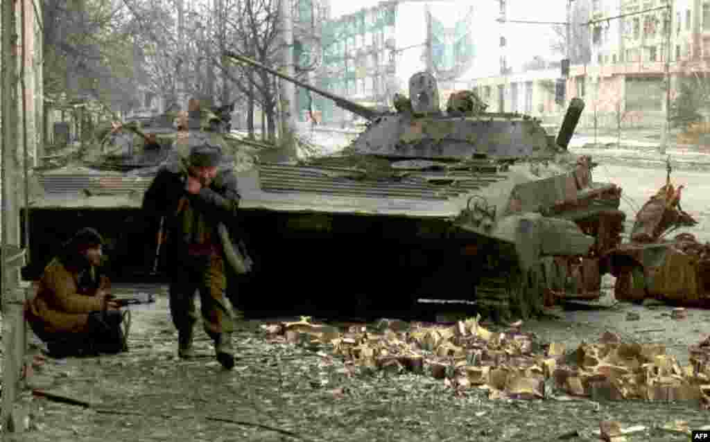 Chechen fighters near destroyed Russian tanks on January 10. In the first stages of the war, one column lost 105 out of 120 tanks and armored personnel carriers.