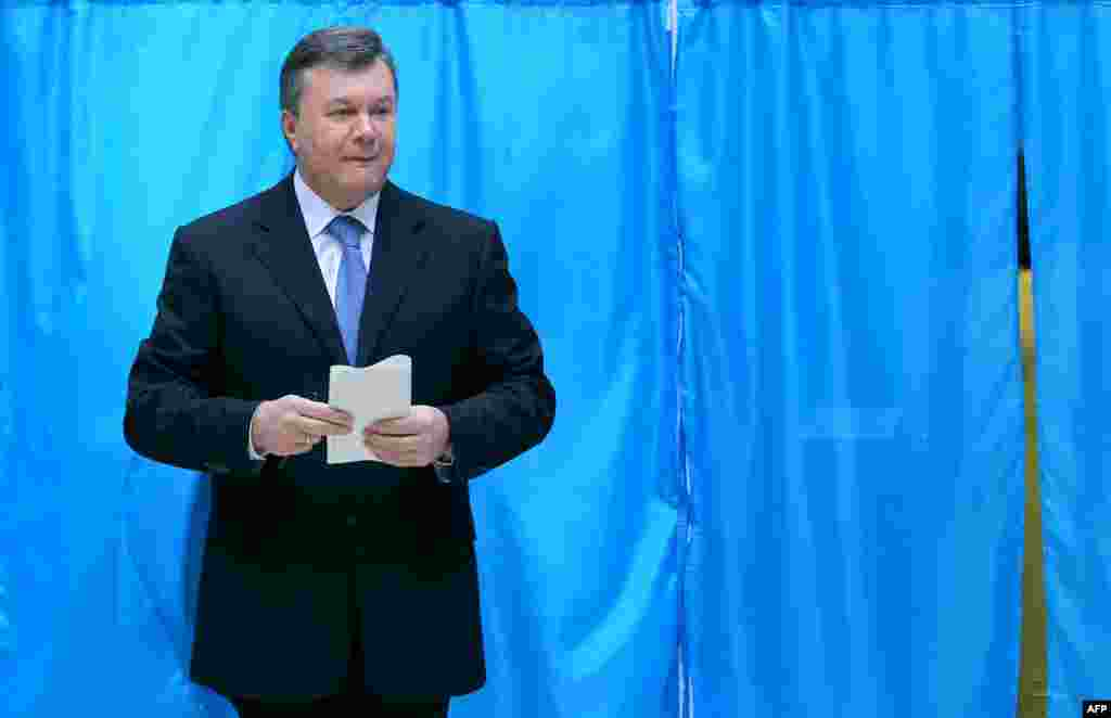 Ukrainian President Viktor Yanukovych holds his ballot at a polling station in Kyiv.