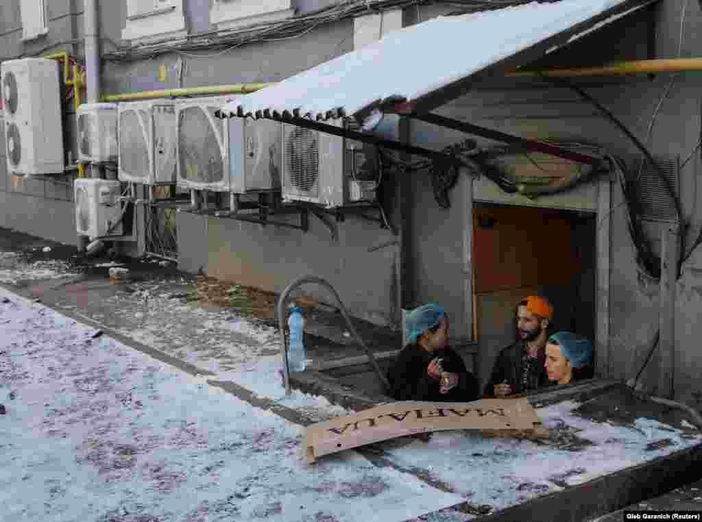 Merkezi Kiýew, restoranyň ýeňse gapysynyň agzynda çilim çekýän işgärler. Ukraina. (Reuters/Gleb Garanich)