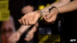 Amnesty International activists wear handcuffs during a protest against the arrest of rights activists in Turkey, including Amnesty International's Turkey director, near the Coliseum in Rome, on July 20.