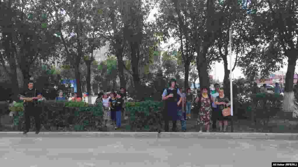 """Пришедшие на церемонию прощания к магазину """"Паллада"""" люди и полицейская охрана. Актобе, 8 июня 2016 года."""