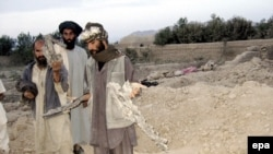 Afghan men show pieces of missiles that they say struck their village in Farah Province.