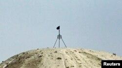 Steagul grupării Statul Islamic la pe un deal la granița dintre Siria și Turcia, 24 septembrie 2014.